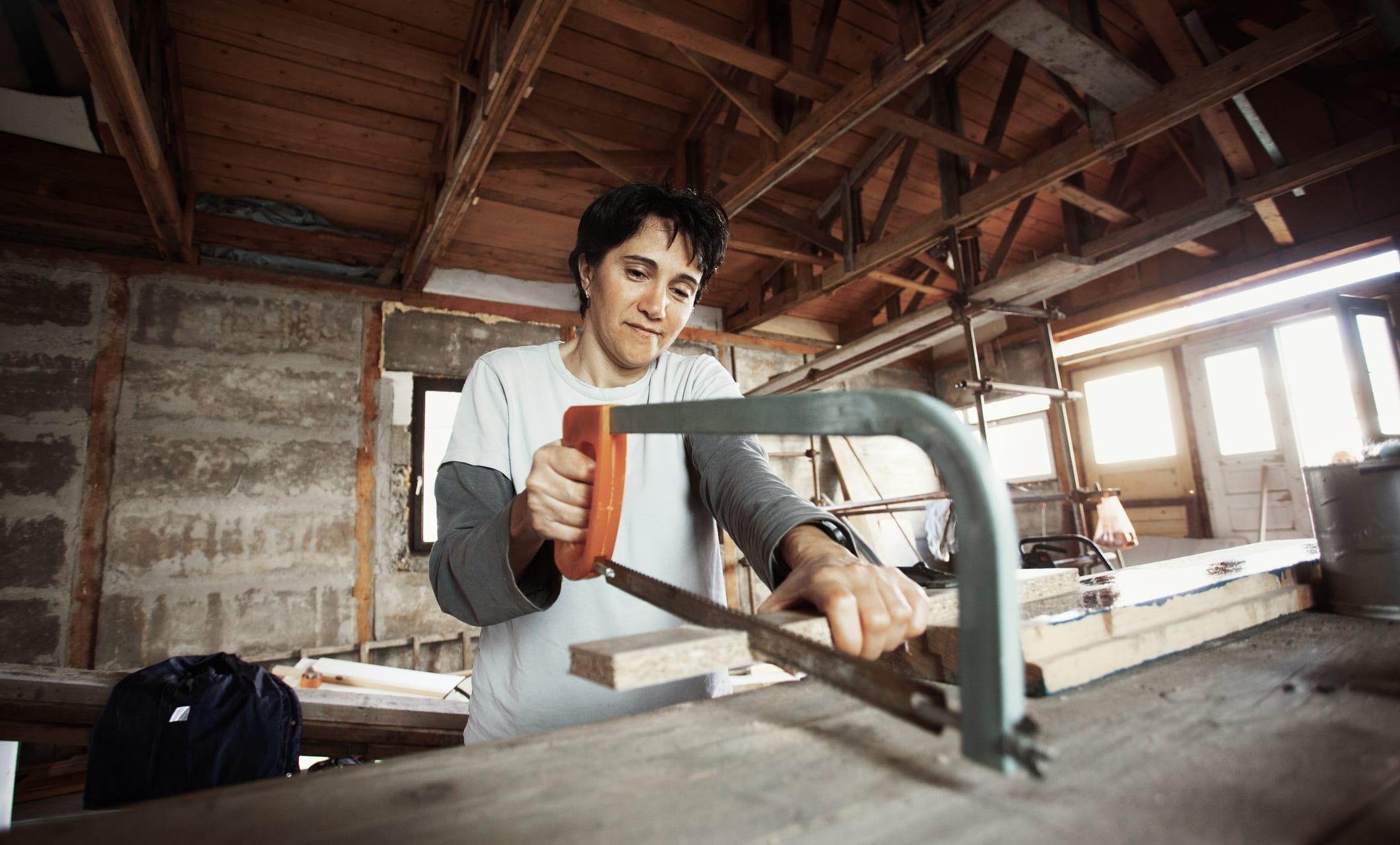 Woman Using Hand saw