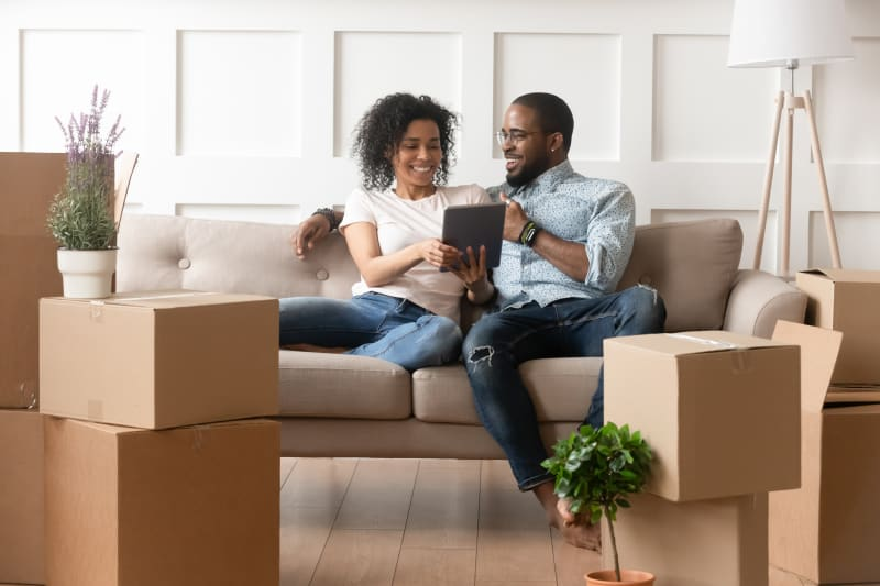 Couple Sits on a Couch and Looks at Tablet
