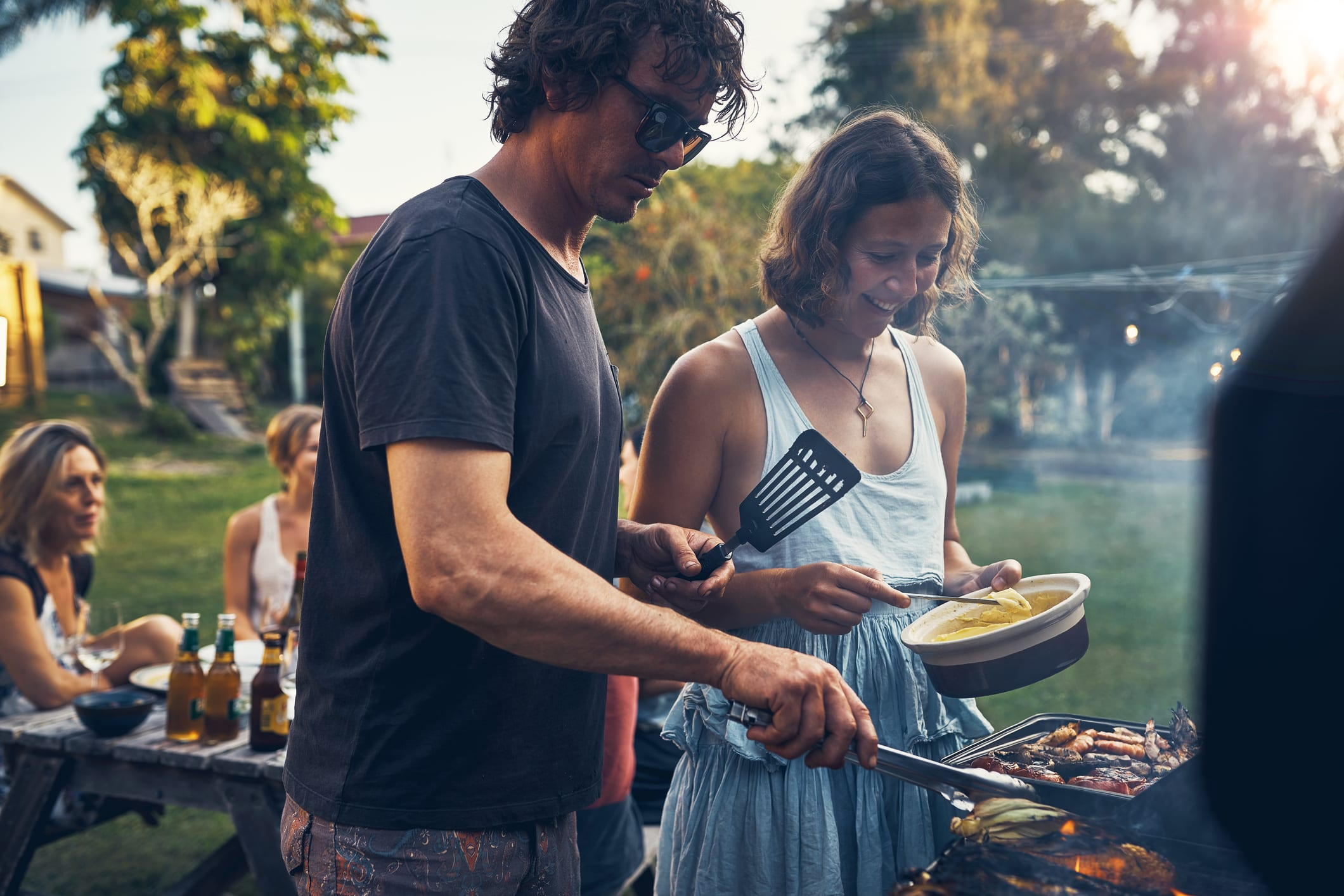 man and woman grilling food