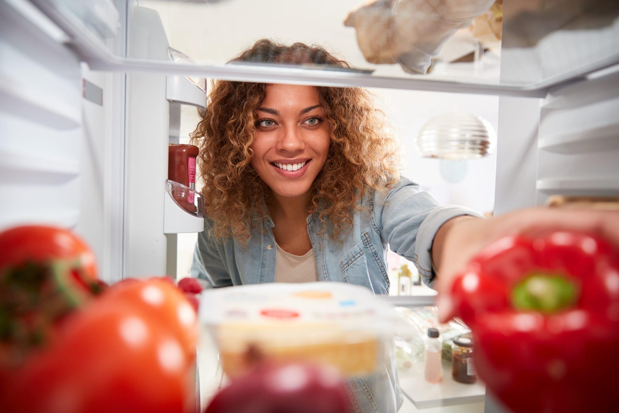 woman puts food into fridge